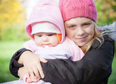Two little sister girls in the park. Outdoor portrait — Stock Photo