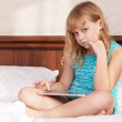 Stock Photo: Little blond girl seat in bed with tablet computer