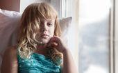 Kleine blonde verschlafenen Mädchen Sitz mit Kissen auf der Fensterbank im hellen Morgenlicht — Stockfoto