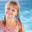 Portrait of a smiling little blond beautiful Russian girl with bright blue pool water — Stock Photo