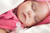 Baby girl sleeps under pink and white cotton towels — Stock Photo