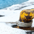 Old rusted yellow mooring bollard with naval rope and snow — Stock Photo