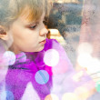 Little blond girl beyond frozen shop window glass — Stock Photo