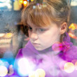 Little blond girl looks through frozen shop window glass — Stock Photo