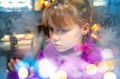 Kleines blondes mädchen schaut durch gefrorene shop fenster-glas — Stockfoto
