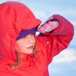 Little ruddy nice girl in winter outwear with hood looks into the distance — Stock Photo #17654795