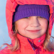 Little ruddy nice girl in winter outwear smiles — Zdjęcie stockowe #17654803