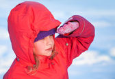 Little ruddy nice girl in winter outwear with hood looks into the distance — Stock Photo