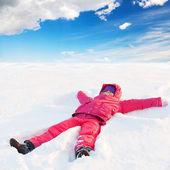 Wenig blutrote nettes mädchen im winter mit kapuze liegt im schnee und lächelt outwear — Stockfoto