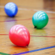 Stock Photo: Three colorful balloons on wooden floor of sports hall. Concept of RGB color scheme
