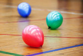 Three colorful balloons on wooden floor of sports hall. Concept of RGB color scheme — Stock Photo