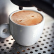 White ceramic cup of fresh espresso with foam in the coffee machine. - Foto de Stock