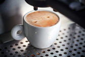 White ceramic cup of fresh espresso with foam in the coffee machine. — Stock Photo