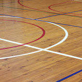 Wooden floor of sports hall with marking lines — Stock Photo
