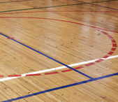 Wooden floor of sports hall with colorful marking lines — Stock Photo
