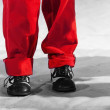 Fun man's legs with red pants and black white shoes — Stock Photo