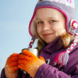 Smiling little blond girl in cold season wears winter outwear with metal cup — Stock Photo