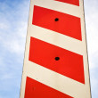 Vertical red white stripped road sign on corner of construct — Stock Photo #18060023