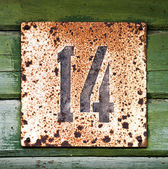 Vintage wooden wall with grunge house number — Stock Photo