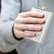 Closed steel small flask in man's hand — Photo