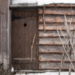 Old wooden building facade with locked door — Stock Photo