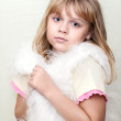 Little blond girl wraps up in white fluffy fur vest — Stock Photo