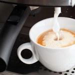 Coffee maker pouring hot milk foam to prepare cappuccino — Stock Photo