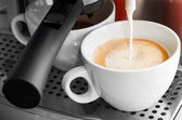 Coffee maker pouring hot milk in white cup — Stock Photo