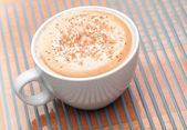 Cappuccino coffee with spice in a white cup — Stock Photo