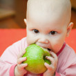 Little baby in a pink jacket eats green apple — Stock Photo