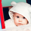 Little baby in white bear costume looks through the window on a playground — Zdjęcie stockowe