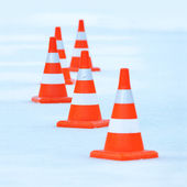 Red and white striped cones on the ice — Stock Photo