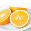 Sliced fresh orange fruit on a white plate — Stock Photo