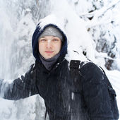 Young Caucasian man stays and smiles under falling snow — Foto Stock