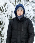 Young Caucasian man stays in winter forest — Stok fotoğraf