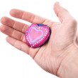 Handmade pink painted heart shaped stone as a gift in man's hand isolated on white — Foto Stock