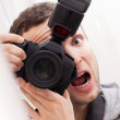 Portrait of fun expressive male photographer with camera - Stock Photo