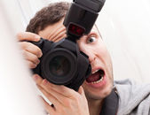 Portrait of fun expressive male photographer with camera — Stock Photo