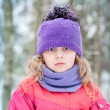Royalty-Free Stock Photo: Little blond girl in winter outwear with snowflakes above forest background