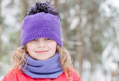 Little beautiful blond girl in winter outwear with snowflakes above forest background — Foto Stock