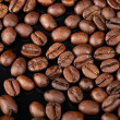Background texture of roasted coffee beans on black background - Stock Photo