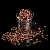 Mug made of glass with whole roasted coffee beans on black background — Stock Photo