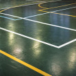 Green floor of sports hall with marking lines — Stock Photo