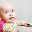 Little baby in casual colorful striped clothing with mobile phone and smiles — Stock Photo