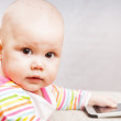 Stock Photo: Little baby in colorful striped clothing with mobile phone looks in camera
