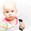 Little baby in casual colorful striped clothing plays with mobile phone — Stock Photo