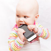 Little baby baby chews on a mobile phone in colorful striped clothing — Stock Photo