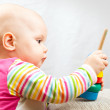 Little baby plays with wooden toy — Stock Photo