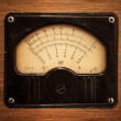 Close-up photo of an vintage electric multimeter on wooden panel - Stock Photo