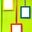 Colorful empty wooden frames on green wall — Stock Photo